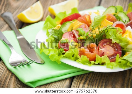 Mixed salad with slices of salmon and honey - mustard sauce on a wooden background - stock photo