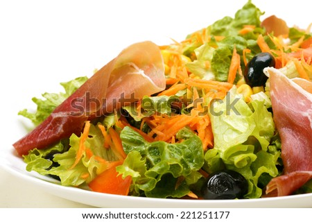 Mixed salad with tomatoes, lettuce, carrot, olive, corn beans and prosciutto
