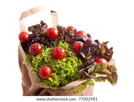 Mixed salat with tomatoes in paper bag over white