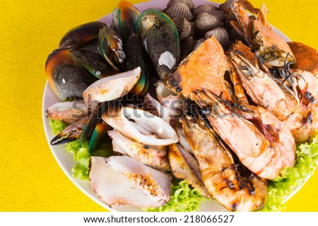 mixed seafood on yellow restaurant table background