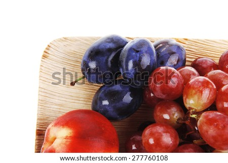 mixed set of fresh raw ripe fruits apple peach grape and plum on light wooden plate isolated over white background - stock photo