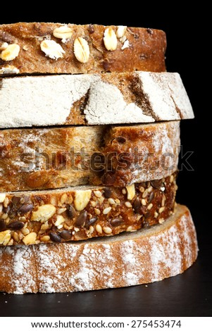 Mixed slices of health breads stacked. On black surface. - stock photo