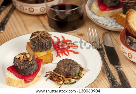 Mixed Spanish tapas with morcilla, pine nuts, confit potato, bread, toast, piquillo pepper, red, wine, rioja. - stock photo