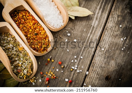 mixed spices for fish and chicken cooking and salt in wooden scoops, bay leaves and pepper corns on old vintage table - stock photo