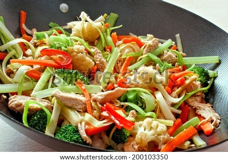 Mixed stir fry vegetables with chicken in a wok - stock photo