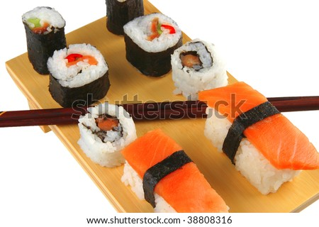 mixed sushi rolls on wooden plate over white