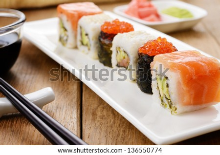 Mixed sushi set on a white plate with soy sauce wasabi and ginger - stock photo