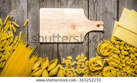 Mixed types of pasta and spaghetti with an empty plate.  On wooden background. Free space for text . Top view - stock photo