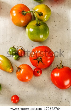 Mixed varieties of homegrown tomatoes rest on an old, worn vintage metal baking sheet. - stock photo