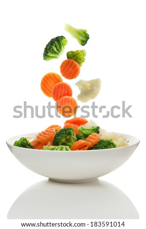 Mixed vegetables falling into a bowl of salad - stock photo