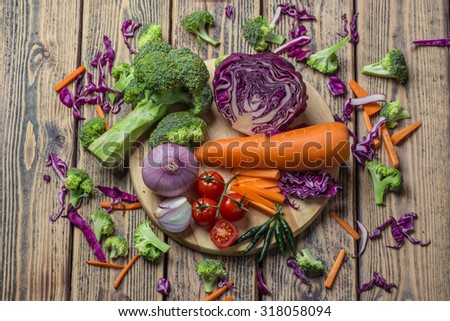 Mixed Vegetables have a carrots, broccoli, Purple cabbage, tomato, onion, chilli on cutting board and around. - stock photo
