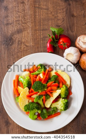 Mixed vegetables in a plate on wooden table - stock photo