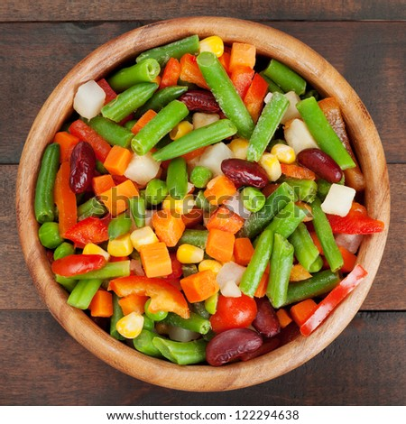 mixed vegetables in wooden bowl on kitchen table, top view - stock photo