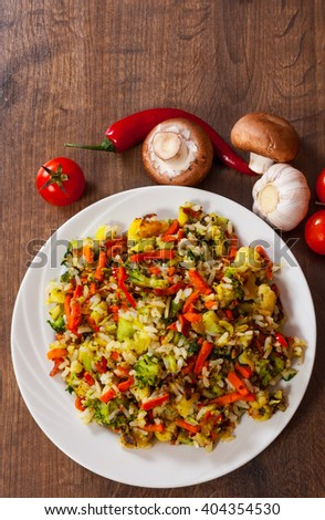 Mixed vegetables with rice in a plate on wooden table
