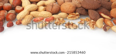 Mixed whole and shelled nuts in a horizontal banner including hazelnuts, brazil nuts, peanuts or groundnuts and walnuts on white with copyspace below - stock photo