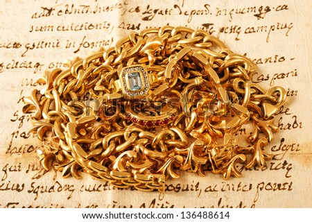 Mixed yellow gold jewelry on a letter - stock photo