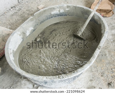 Mixing a cement in salver for applying construction  - stock photo