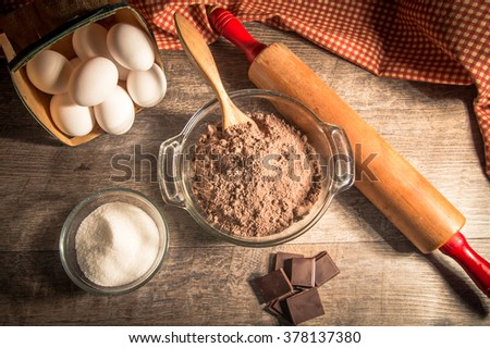 Mixing A Chocolate Cake. Preparing chocolate cake batter surrounded by fresh ingredients, wooden spoon and chocolate. - stock photo