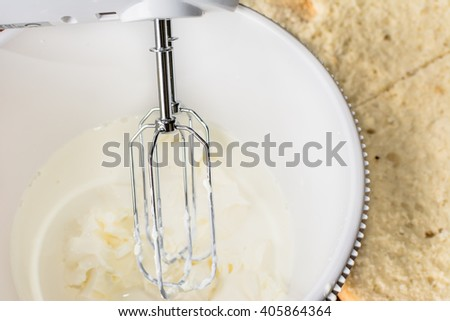 Mixing a whipped cream for a sponge cake in a bowl with electric mixer. Preparing a torte. - stock photo