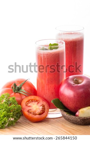 mixing apple and tomato into healthy juice