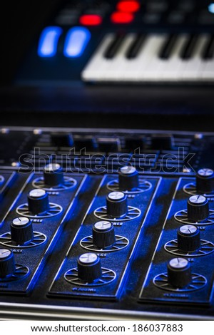 mixing board and synthesizer in a studio
