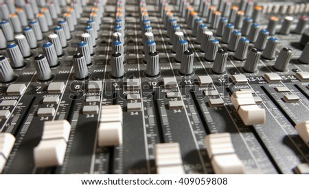 Mixing Board Faders and Knobs. Pro audio mixing board faders and knobs, multi-track music recording equipment.