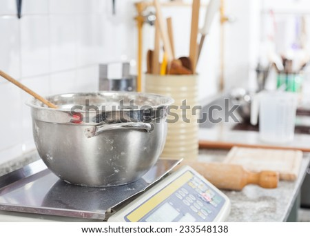 Mixing bowl on weight scale at counter in commercial kitchen - stock photo