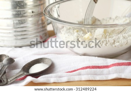 Mixing bowl with butter and flour, vintage sifter and measuring spoons on a dish towel - stock photo