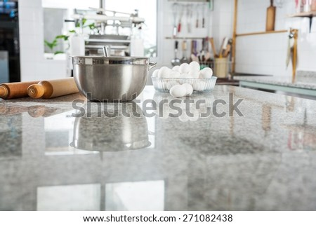 Mixing bowl with eggs and rolling pin on marble counter top in commercial kitchen - stock photo