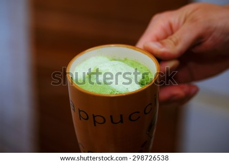 Mixing Green Barley Grass Powder in man hand. Juice for Vitality & Health  - stock photo