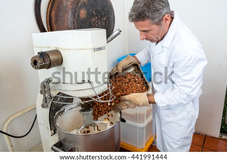 mixing of roasted almonds in honey and glucose for French sweet nougat specialty by male craftsman, into industrial bowl in laboratory background