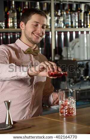Mixology in action. Vertical shot of positive bartender concentrating on working.