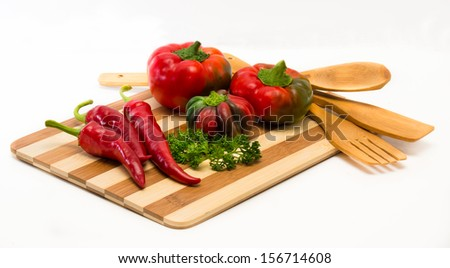 Mixture of chilli and sweet peppers and wood on the board with wooden spoons.