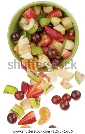Mixture of fresh fruit pieces with bowl on white background
