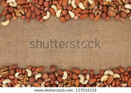 Mixture of nuts lying on sackcloth with space for text - stock photo
