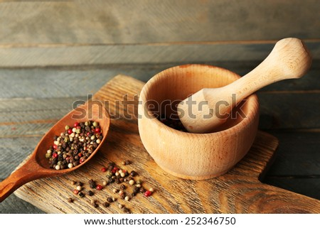 Mixture of peppers in mortar on wooden background - stock photo