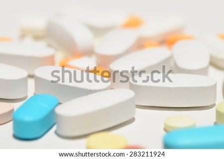 Mixture of pills and drugs on white background