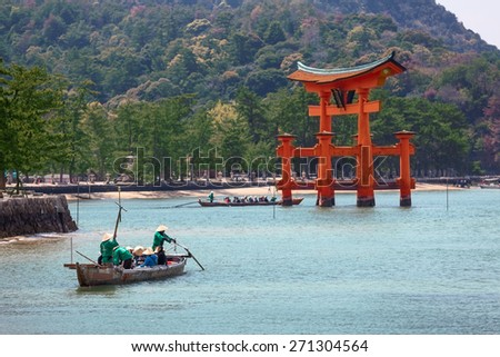 MIYAJIMA, JAPAN - CIRCA APR, 2013: Old-fashioned boat with visitors is in bay during excursion to red wooden sacred torii gate at sea high tide. The Miyajima Island (Itsukushima), Japan - stock photo