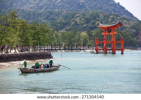 MIYAJIMA, JAPAN - CIRCA APR, 2013: Small boat with visitors is in bay during excursion to red wooden sacred torii gate at sea high tide. The Miyajima Island (Itsukushima), Japan - stock photo