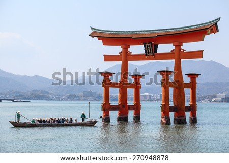 MIYAJIMA, JAPAN - CIRCA APR, 2013: Tourists have boat cruise under sacred torii gate at sea high tide. The Miyajima Island (Itsukushima), Japan - stock photo