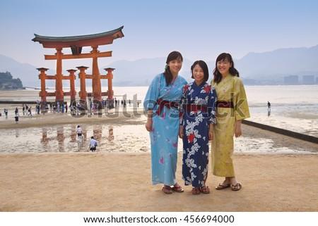 MIYAJIMA, JAPAN - MAY 27: Asian Tourists in front of famous floating torii gate of the Itsukushima Shrine on Miyajima at sunset on May 27,2016 in Miyajima, Japan - stock photo
