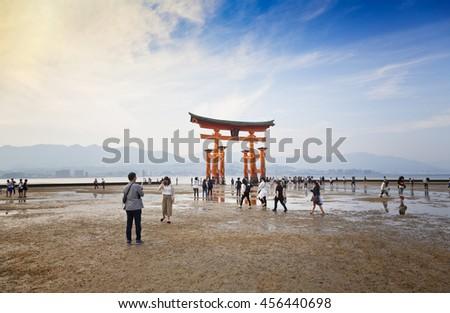 MIYAJIMA, JAPAN - MAY 27: Tourists walk around the famous floating torii gate of the Itsukushima Shrine on Miyajima at low tide shown on May 27,2016 in Miyajima, Japan - stock photo