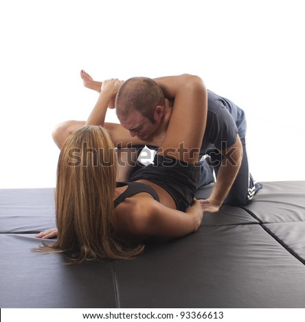 MMA female fighter demonstrating a Jiu-Jitsu ankle choke - stock photo