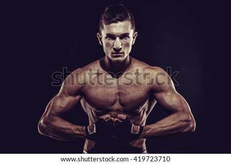 MMA Fighter Preparing Bandages For Training. Darck background