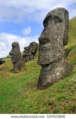 Moai sit on Easter Island on February 6, 2012. The giant monuments were carved from volcanic stone and face away from the mythical spirit world of the sea. - stock photo