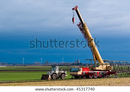 Mobil crane preparing for assembling transmission towers and wind turbines on the background - stock photo