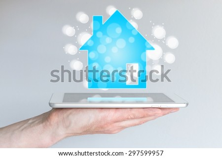 Mobile and online real estate and property sales with smart phone and tablet. Hand holding modern smart phone or tablet.