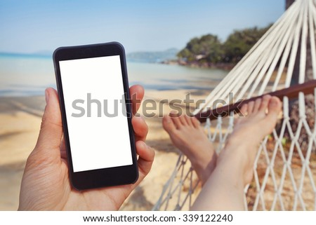 mobile application for travels, hand holding smart phone with white screen on the beach - stock photo