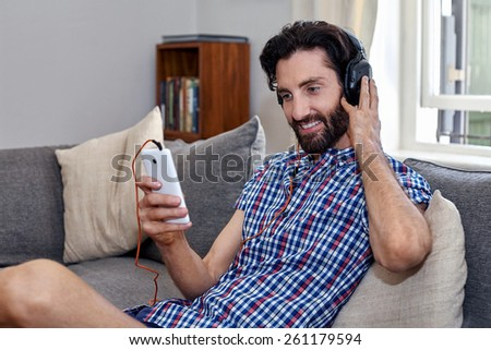 mobile cellphone man listening music sofa couch at home living room - stock photo