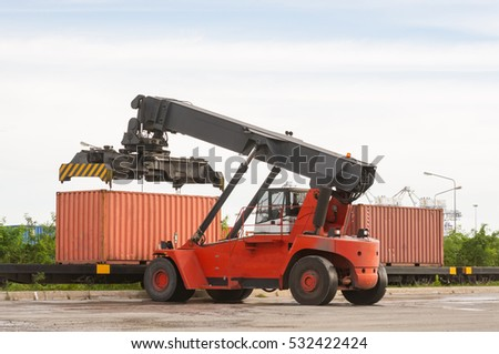 Mobile crane lifting container box to support goods trains for import, Export to international, cloudy sky background.